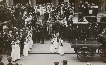 The Funeral procession of Emily Wilding Davison, 14 June 1913. On 4th June 1913 the suffragette Emily Wilding Davison ran onto the Derby race course in an attempt to stop the King's horse. Seriously injured, she never regained consciousness, and died four days later. Emily's spectacular funeral procession through the streets of London organised by the suffragette leaders was intended to raise Emily to the status of martyr. This image shows Emily's coffin being taken into St George's Church in Bloomsbury where a memorial service was held. The coffin was subsequently transported to King's Cross station and on by train to the Davison family home of Morpeth, Northumberland for a family funeral. Photograph by H. Searjeant